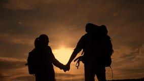 Ευτυχείς οικογενειακοί τουρίστες που περπατούν τη σκιαγραφία χεριών εκμετάλλευσης στο ηλιοβασίλεμα τρόπος ζωής έννοιας ταξιδιού ο φιλμ μικρού μήκους