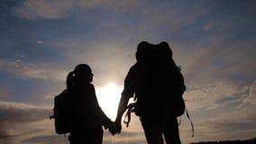 Ευτυχείς οικογενειακοί τουρίστες που περπατούν τη σκιαγραφία χεριών εκμετάλλευσης στο ηλιοβασίλεμα Έννοια ταξιδιού ομαδικής εργασ φιλμ μικρού μήκους