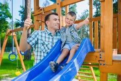 Ευτυχείς παιδί και πατέρας που έχουν τη διασκέδαση Παιδί με το παιχνίδι μπαμπάδων Στοκ φωτογραφία με δικαίωμα ελεύθερης χρήσης