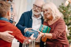 ευτυχείς παππούδες και γιαγιάδες που παρουσιάζουν τα όμορφα δώρα Στοκ εικόνα με δικαίωμα ελεύθερης χρήσης