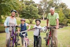 Ευτυχείς παππούδες και γιαγιάδες με τα εγγόνια τους στο ποδήλατό τους Στοκ Εικόνες