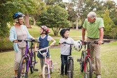 Ευτυχείς παππούδες και γιαγιάδες με τα εγγόνια τους στο ποδήλατό τους Στοκ φωτογραφία με δικαίωμα ελεύθερης χρήσης