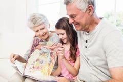Ευτυχείς παππούδες και γιαγιάδες με την εγγονή που διαβάζει ένα βιβλίο Στοκ Φωτογραφία