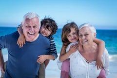 Ευτυχείς παππούδες και γιαγιάδες που δίνουν piggyback στα παιδιά Στοκ Εικόνες