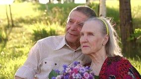 Ευτυχείς παππούδες και γιαγιάδες που κάθονται στο πάρκο στη χλόη φιλμ μικρού μήκους