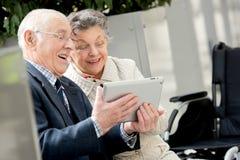 Ευτυχείς παππούδες και γιαγιάδες που χρησιμοποιούν την ταμπλέτα Στοκ εικόνες με δικαίωμα ελεύθερης χρήσης
