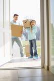 Ευτυχείς πατέρας και γιος με τα κουτιά από χαρτόνι που εισάγονται στο καινούργιο σπίτι Στοκ φωτογραφία με δικαίωμα ελεύθερης χρήσης