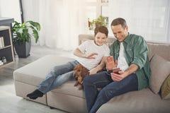 Ευτυχείς πατέρας και γιος που έχουν την επικοινωνία Διαδικτύου στο σπίτι στοκ εικόνες