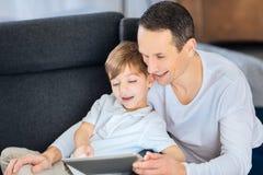 Ευτυχείς πατέρας και γιος που συνδέουν χρησιμοποιώντας την ταμπλέτα από κοινού Στοκ εικόνα με δικαίωμα ελεύθερης χρήσης