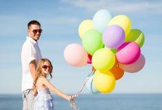 Ευτυχείς πατέρας και κόρη με τα ζωηρόχρωμα μπαλόνια Στοκ εικόνες με δικαίωμα ελεύθερης χρήσης