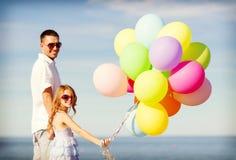 Ευτυχείς πατέρας και κόρη με τα ζωηρόχρωμα μπαλόνια Στοκ Εικόνα