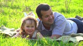 Ευτυχείς πατέρας και κόρη που στηρίζονται στη χλόη φιλμ μικρού μήκους