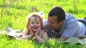 Ευτυχείς πατέρας και κόρη που στηρίζονται στη χλόη απόθεμα βίντεο