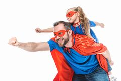 ευτυχείς πατέρας και κόρη στα κοστούμια superhero που προσποιούνται να πετάξει στοκ εικόνες