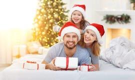 Ευτυχείς πατέρας και παιδί familymother στο πρωί Χριστουγέννων στο κρεβάτι Στοκ Φωτογραφία