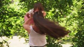 Ευτυχείς περιστροφές μητέρων με το μωρό στο ηλιόλουστο θερινό πάρκο απόθεμα βίντεο