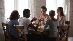Ευτυχείς πολυφυλετικοί νέοι φίλοι που μιλούν τρώγοντας την πίτσα που μοιράζεται τον πίνακα καφέδων απόθεμα βίντεο