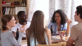 Ευτυχείς πολυφυλετικοί φίλοι που τρώνε την μπύρα κατανάλωσης πιτσών που μιλά στο pizzeria απόθεμα βίντεο