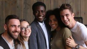 Ευτυχείς πολυ-εθνικοί νέοι που συνδέουν την τοποθέτηση για τη φωτογραφία πορτρέτου ομάδας απόθεμα βίντεο