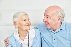 Ευτυχείς πρεσβύτεροι ζευγών που αγκαλιάζουν ο ένας τον άλλον στο σπίτι Στοκ Φωτογραφίες