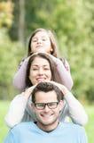 Ευτυχείς πρόγονοι με την όμορφη κόρη στο πάρκο. στοκ φωτογραφία