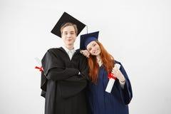 Ευτυχείς πτυχιούχοι των πανεπιστημιακών θέτοντας holsing διπλωμάτων χαμόγελου πέρα από το άσπρο υπόβαθρο Στοκ Εικόνες