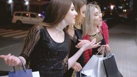 Ευτυχείς πωλήσεις παραθύρων λεωφόρων αγορών νύχτας κοριτσιών απόθεμα βίντεο