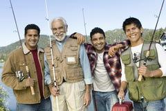 Ευτυχείς ράβδοι αλιείας πατέρων και εκμετάλλευσης γιων Στοκ Εικόνες