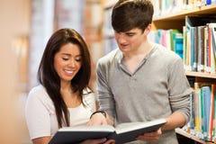 Ευτυχείς σπουδαστές που εξετάζουν ένα βιβλίο στοκ εικόνα