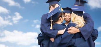 Ευτυχείς σπουδαστές ή άγαμοι που αγκαλιάζουν πέρα από το μπλε ουρανό Στοκ Εικόνες