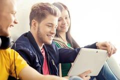 Ευτυχείς σπουδαστές με έναν υπολογιστή ταμπλετών Στοκ εικόνες με δικαίωμα ελεύθερης χρήσης