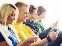 Ευτυχείς σπουδαστές με τα smartphones σε ένα σπάσιμο Στοκ Εικόνα