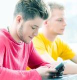 Ευτυχείς σπουδαστές με τα smartphones Στοκ εικόνα με δικαίωμα ελεύθερης χρήσης