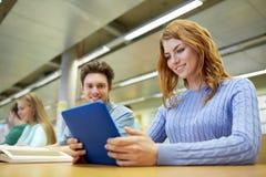 Ευτυχείς σπουδαστές με το PC ταμπλετών στη βιβλιοθήκη Στοκ Εικόνα