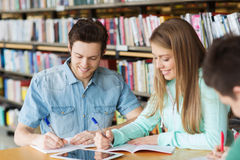 Ευτυχείς σπουδαστές που γράφουν στα σημειωματάρια στη βιβλιοθήκη Στοκ εικόνες με δικαίωμα ελεύθερης χρήσης