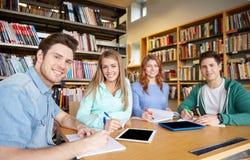 Ευτυχείς σπουδαστές που γράφουν στα σημειωματάρια στη βιβλιοθήκη στοκ φωτογραφία