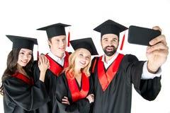 Ευτυχείς σπουδαστές που παίρνουν selfie στο smartphone που απομονώνεται στο λευκό Στοκ φωτογραφία με δικαίωμα ελεύθερης χρήσης