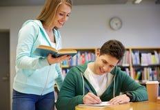 Ευτυχείς σπουδαστές που προετοιμάζονται στους διαγωνισμούς στη βιβλιοθήκη Στοκ εικόνες με δικαίωμα ελεύθερης χρήσης