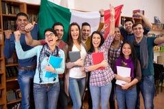 Ευτυχείς σπουδαστές που χαμογελούν και που παρουσιάζουν στην ιταλική χώρα με τη σημαία Στοκ εικόνα με δικαίωμα ελεύθερης χρήσης
