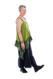 Ευτυχείς στάσεις ηλικιωμένων γυναικών στο ρέοντας μακρύ φόρεμα στοκ εικόνες