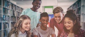 Ευτυχείς συμμαθητές που χρησιμοποιούν την ψηφιακή ταμπλέτα στη βιβλιοθήκη στοκ φωτογραφία