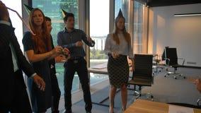 Ευτυχείς συνάδελφοι που γιορτάζουν τα γενέθλια στο σύγχρονο coworking γραφείο Serpentine, σωλήνες απόθεμα βίντεο