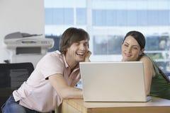 Ευτυχείς συνάδελφοι με το lap-top στο γραφείο στοκ φωτογραφία