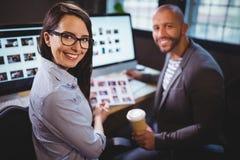 Ευτυχείς συνάδελφοι που κάθονται στο γραφείο υπολογιστών στο δημιουργικό γραφείο Στοκ εικόνα με δικαίωμα ελεύθερης χρήσης