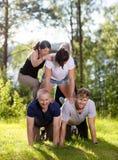 Ευτυχείς συνάδελφοι που κάνουν την ανθρώπινη πυραμίδα στο χλοώδη τομέα Στοκ Εικόνα