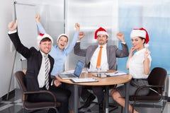Ευτυχείς συνάδελφοι στον εορτασμό καπέλων santa Στοκ Φωτογραφίες