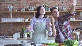 Ευτυχείς σύζυγος ζευγών και μάγειρας συζύγων στην κουζίνα που χορεύει και που τραγουδά φιλμ μικρού μήκους
