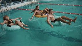 Ευτυχείς τέσσερις φίλοι που κολυμπούν στα διογκώσιμα λαστιχένια δαχτυλίδια στην ομάδα του ξενοδοχείου πολυτελείας 4K απόθεμα βίντεο