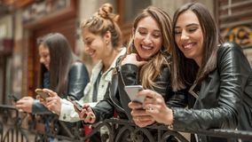 Ευτυχείς τέσσερις φίλοι που προσέχουν τα κοινωνικά μέσα Διαδικτύου στο τηλέφωνο κυττάρων Στοκ Εικόνα
