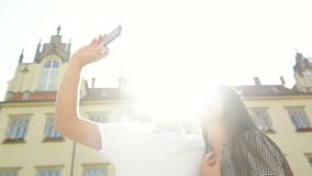 Ευτυχείς ταξιδιώτες που παίρνουν Selfie χρησιμοποιώντας Smartphone που στέκεται στο παλαιό τετράγωνο πόλεων στο υπόβαθρο κτηρίων  απόθεμα βίντεο